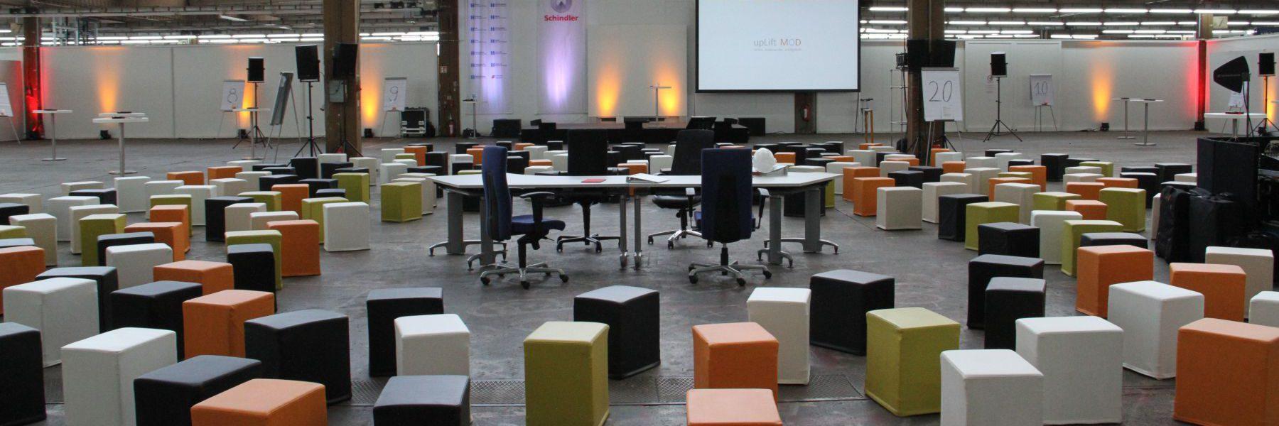 SWOOFLE Mietmöbel Europaweit Overnight - in Industriehalle bunt gewürfelt